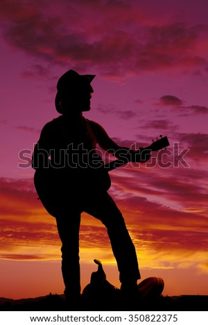 A silhouette of a cowboy with his foot on his saddle, playing his guitar in the outdoors. - stock photo