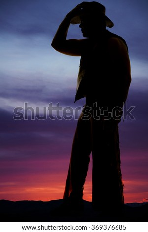 A silhouette of a cowboy with his hand on his hat looking.