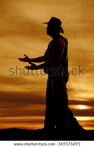 A silhouette of a cowboy with his hands out looking to the side. - stock photo