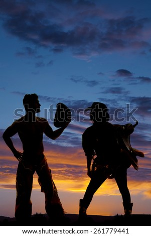 a silhouette of a cowgirl holding her saddle while her cowboy takes off his hat. - stock photo