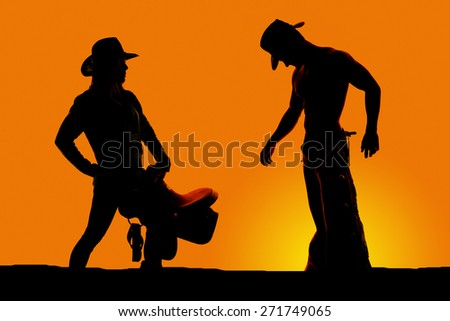 a silhouette of a cowgirl holding her saddle with her cowboy near by. - stock photo