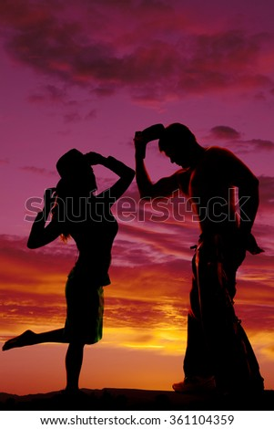 A silhouette of a cowgirl holding on to her hat with her cowboy next to her.