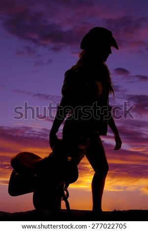 A silhouette of a cowgirl holding on to her saddle walking. - stock photo