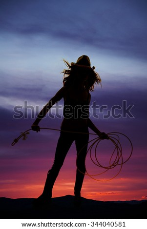 A silhouette of a cowgirl in her western hat holding on to her rope. - stock photo