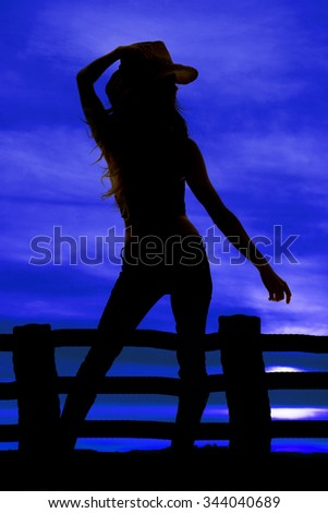 A silhouette of a cowgirl in the outdoors, by a wooden fence, holding on to her hat. - stock photo