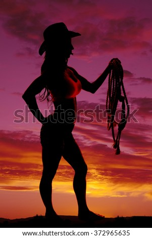 A silhouette of a cowgirl in the sunset with a rope. - stock photo