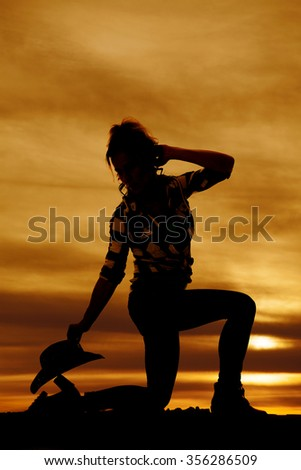 A silhouette of a cowgirl kneeling down with her western hat by her foot. - stock photo