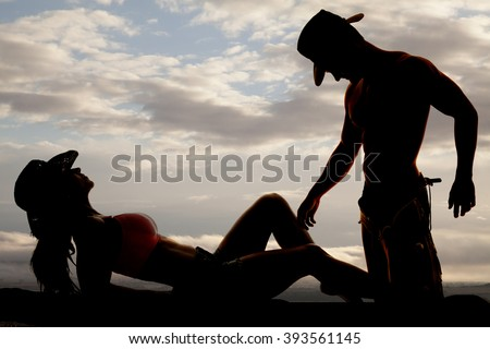 a silhouette of a cowgirl laying back with her cowboy touching her leg with his hand. - stock photo