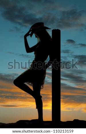 A silhouette of a cowgirl leaning back on a post holding onto her hat with a colorful sky behind her. - stock photo