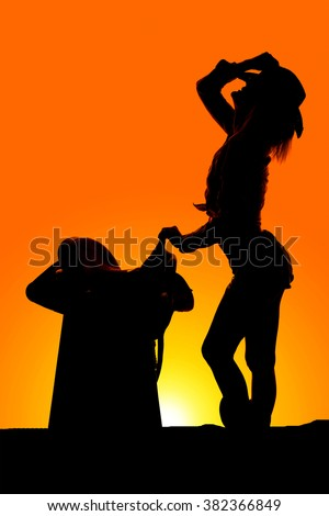 A silhouette of a cowgirl leaning back with her hand on her hat. - stock photo
