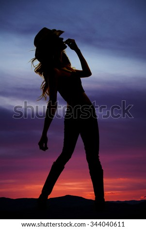 A silhouette of a cowgirl leaning in the outdoors.