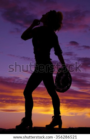 A silhouette of a cowgirl looking up while holding on to her western hat. - stock photo