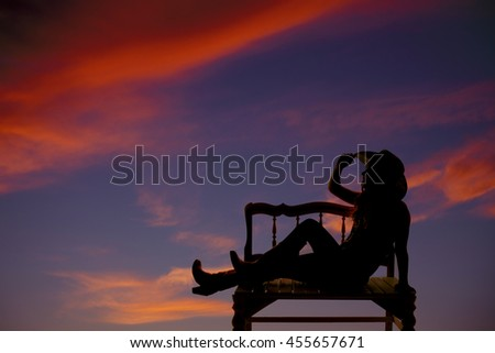 A silhouette of a cowgirl sitting on a bench relaxing with a beautiful sunset. - stock photo