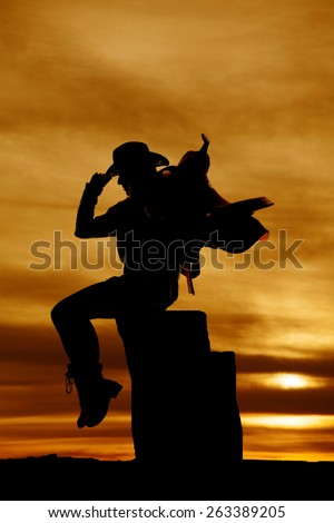 A silhouette of a cowgirl sitting on a log, she is holding on to her saddle. - stock photo