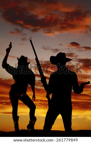 a silhouette of a cowgirl with a pistol in her hand, standing near her cowboy - stock photo