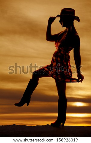 A silhouette of a cowgirl with her leg up in her checkered dress. - stock photo