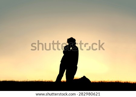 A silhouette of a father lovingly hugging and kissing his young child on the head while isolated against the sunsetting sky on a summer day. - stock photo