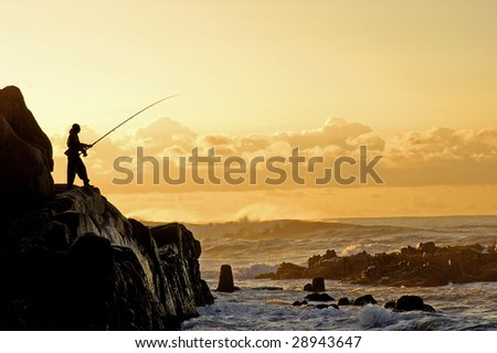 A silhouette of a fisherman at sunrise - stock photo