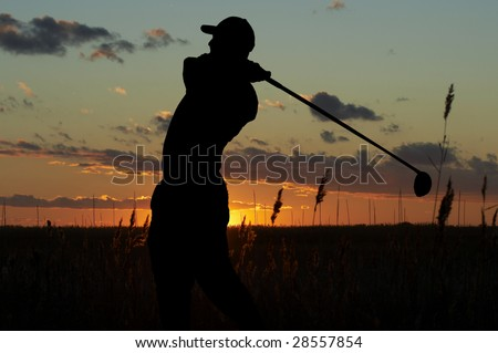 a silhouette of a golfer on a mourning sunset - stock photo