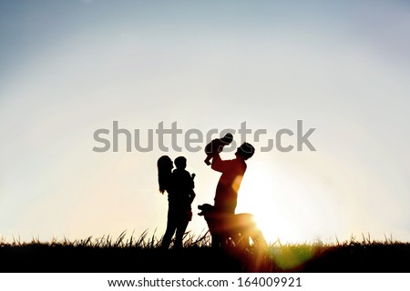 A silhouette of a happy family of four people, mother, father, baby, and child, and their dog in front of a sunsetting sky, with room four copy space or text - stock photo