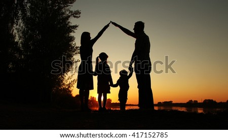 a silhouette of a happy family with children - stock photo