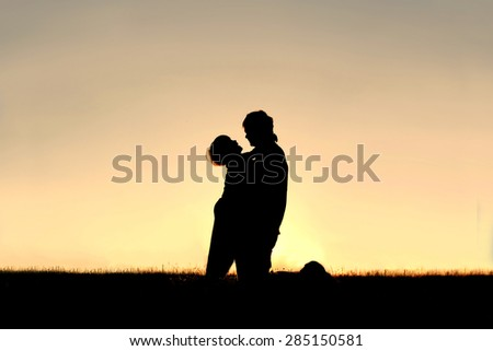 A silhouette of a happy little boy laughing as he hugs his father outside at sunset on a summer day. - stock photo