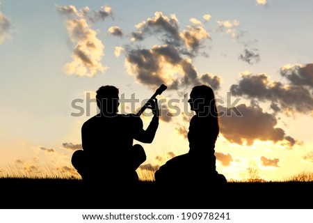 A silhouette of a happy, young couple in love, with the man playing guitar for the woman isolated in front of a beautiful sunset in the sky. - stock photo
