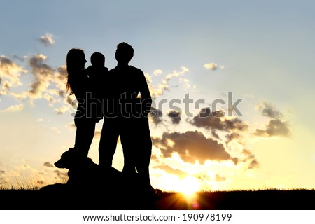 a silhouette of a happy young family of four people; mother, father, child, and baby, stand outside in front of a sunset in the sky with their pet German Shepherd Dog. - stock photo
