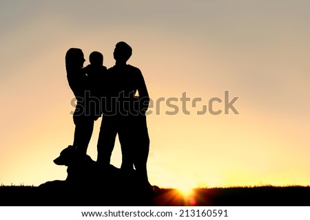 a silhouette of a happy young family of four people; mother, father, child, and baby, stand outside isolated in front of a sunset in the sky with their pet German Shepherd Dog. - stock photo