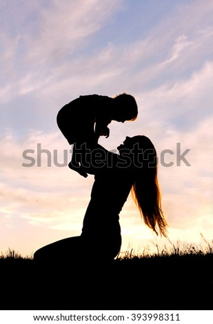 A silhouette of a happy young mother, laughing as she plays with her toddler child and lifts him over her head outside at sunset.