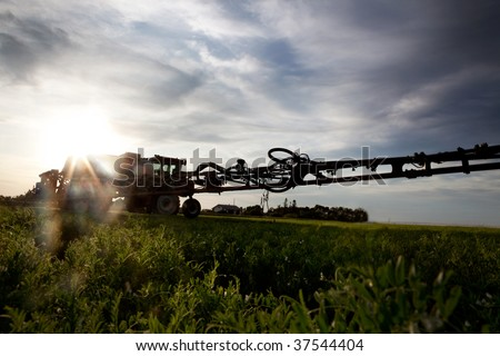A silhouette of a high clearance sprayer on a field with solar flare. - stock photo
