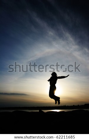 A silhouette of a jumping woman on  sunset background - stock photo