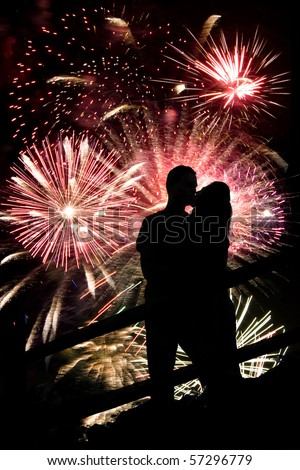 A silhouette of a kissing couple in front of a huge fireworks display. - stock photo