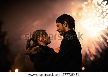 A silhouette of a kissing couple in front of a huge fireworks display. Filtered image with grain - stock photo