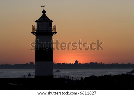 A silhouette of a lighthouse at dusk