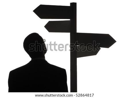 A silhouette of a lost man choosing his destination from the directing boards. - stock photo