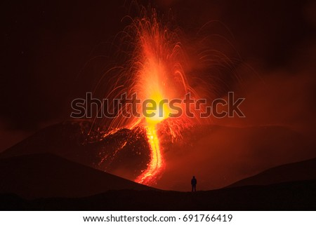 A silhouette of a man admiring the eruption of the mount Etna.