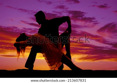A silhouette of a man and woman dancing she is leaning back over his knee. - stock photo