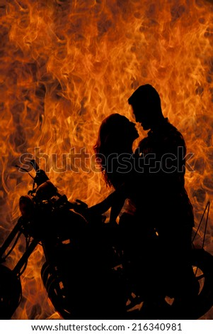 A silhouette of a man and woman holding each other close, getting ready to kiss. - stock photo