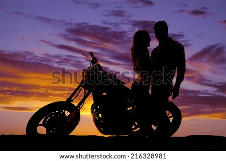 A silhouette of a man and woman next to a motorcycle in the outdoors. - stock photo