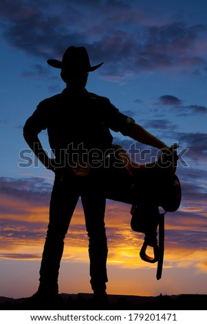 A silhouette of a man cowboy holding a saddle. - stock photo