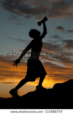 A silhouette of a man going up a hill working out and exercising with weights. - stock photo