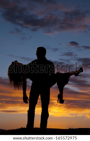 a silhouette of a man holding on to the woman he loves. - stock photo