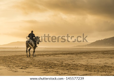 A silhouette of a man horse riding along a beautiful beach in Tarifa Andalusia Spain at sunset. - stock photo
