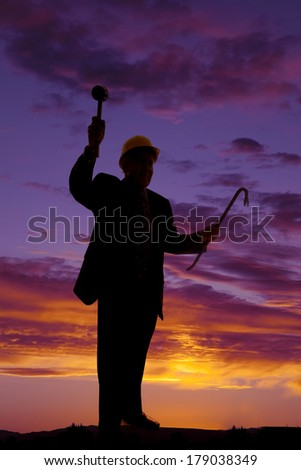A silhouette of a man in his construction hat and using his tools. - stock photo