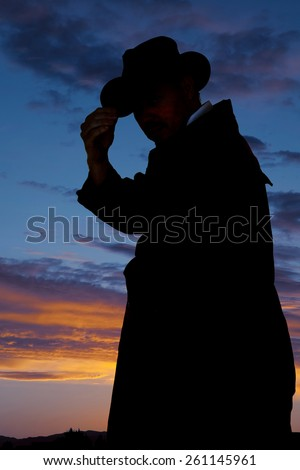 a silhouette of a man in his duster coat touching the brim of his hat looking to the side. - stock photo