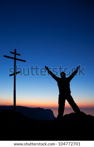 A silhouette of a man near the cross against the sky at sunset - stock photo