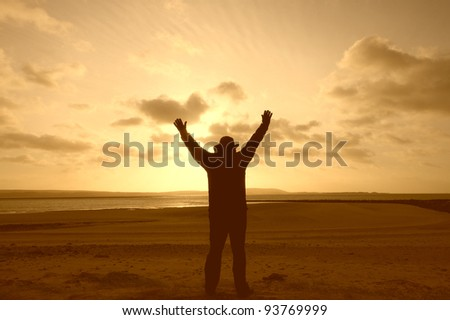 A silhouette of a man on a beach with his arms in the air - stock photo