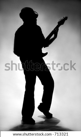 A silhouette of a man playing a guitar.