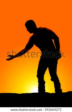 a silhouette of a man reaching out in the outdoors. - stock photo